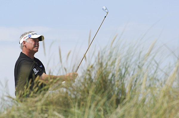 """Darren Clarke grabbed a share of the lead with a birdie on 18. """"There's an awful long way to go yet, and I believe the forecast for the weekend is very, very poor, which I quite look forward to,"""" said Clarke, who is from Northern Ireland."""