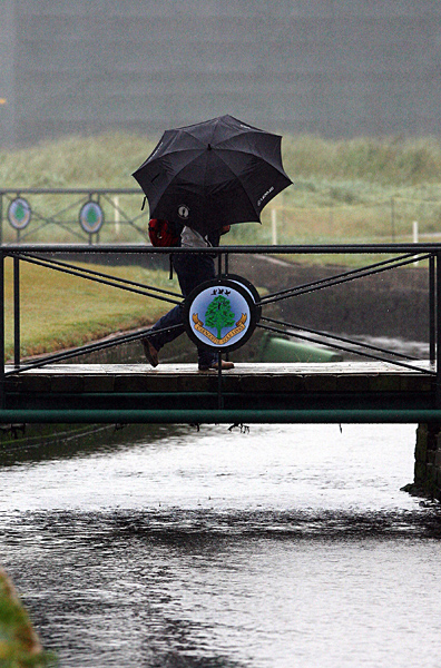 A fan braved the nasty weather during the practice rounds Monday.