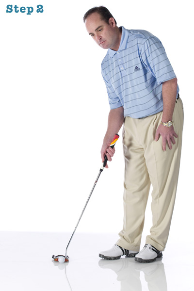 STEP 2 Walk to the ball, still holding the putter in your dominant hand and keeping your eyes focused on your intended line. Set your putter behind the ball and point the face at your target.