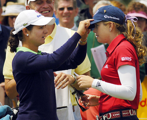 Lorena Ochoa, left, assisted Paula Creamer with her hat prior to the second round.