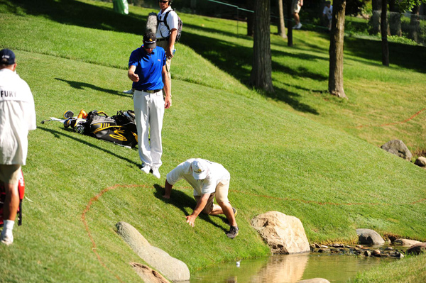 Geoff Ogilvy took a drop after hitting into a creek on 17, but his caddie missed the ball and it fell into the water.