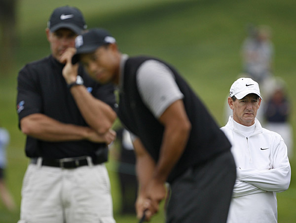 Coach Hank Haney, right, and caddie Steve Williams watched Woods putt on the fifth hole.