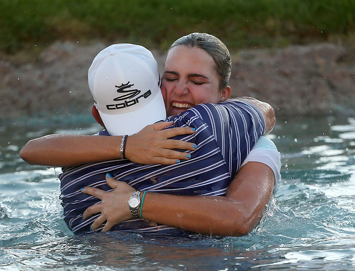Lexi Thompson celebrates with her father Scott Thompson after taking the leap into Poppie's Pond after her victory during the final round of the 2014 Kraft Nabisco Championship.