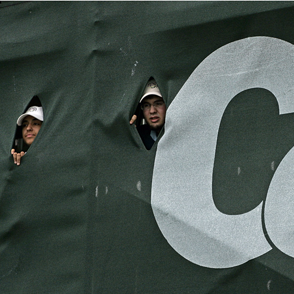 Volunteers peek through the back of a scoreboard to see Tiger Woods on No. 9.