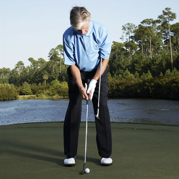 To Link Your Shoulders to Your Chest...                       Wedge the grip of your sand iron underneath your left armpit, grip your putter, and set up to the ball so that the two shafts are parallel. The shaft of your sand iron should rest slightly on top of your left forearm.
