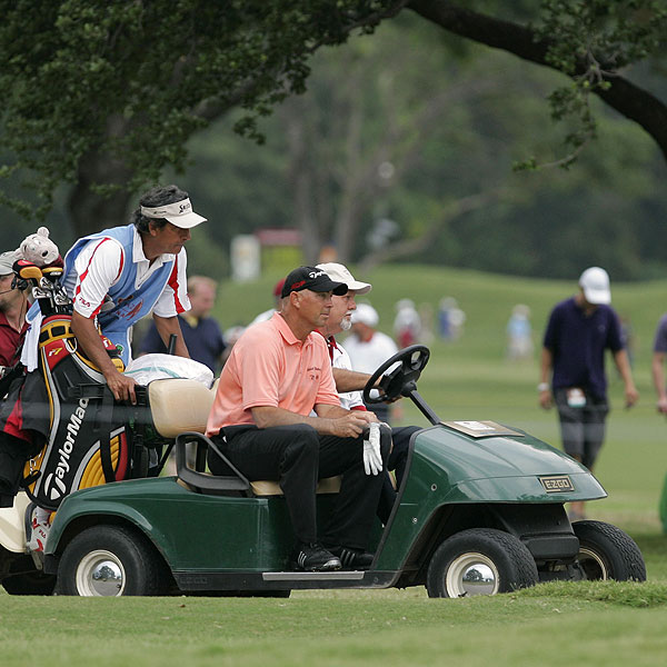 Tom Lehman, front, and others left the course in a cart after the weather siren sound. Lehman is at 3 under par after 6 holes.