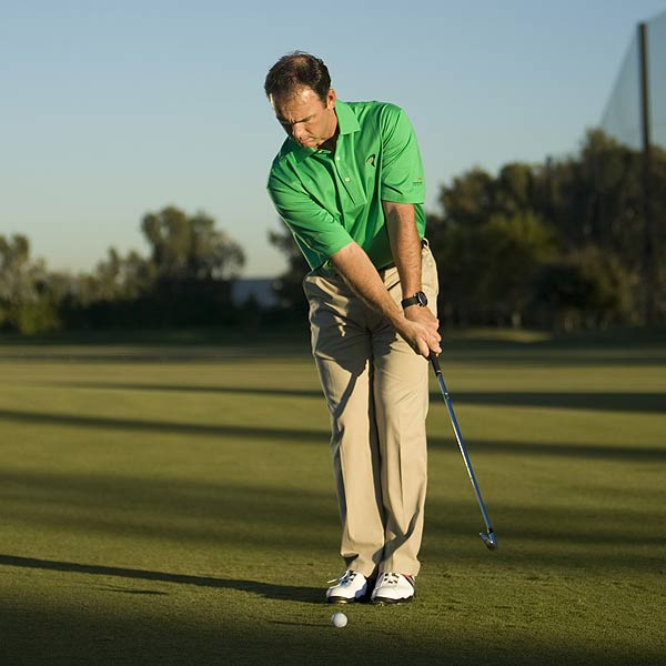 STEP 1                                                      Tee up a ball and use your 9-iron for this drill. Place your feet together with the ball in the middle of your stance and the club about two feet in front of the ball.