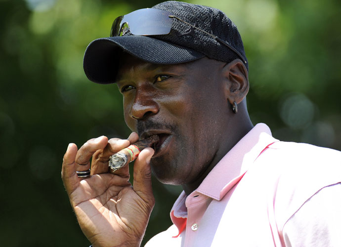 Michael Jordan takes a drag from his cigar during the Canadian Open's Mike Weir pro-am in 2009. Jordan has said he didn't smoke cigars until Chicago Bulls owner Jerry Reinsdorf gave him one to celebrate the team's 1991 NBA championship.