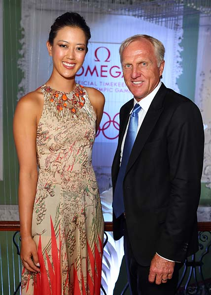 Greg Norman looks tiny next to 6-foot-tall Michelle Wie at an Omega event in 2012.