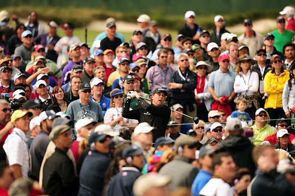 drives off the 10th tee on Sunday with a mob of spectators.