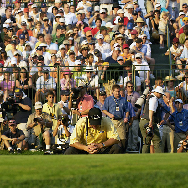 "Standing on the par-4 18th tee in the final round, Phil Mickelson led by one and was on the verge of winning his third consecutive major. But then he suffered one of the most ignominious meltdowns in Open history: a push-slice drive bounced off a corporate tent; a cut three-iron banged off the trunk of a tree and rolled back to his feet; another cut iron shot plugged in a greenside bunker. Mickelson made double bogey and finished a shot behind Geoff Ogilvy. ""I am such an idiot,"" said Mickelson."