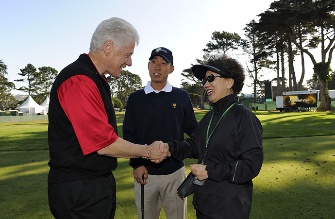 President Bill Clinton meets Anthony Kim and his mom, Miryoung, during practice for The Presidents Cup at Harding Park Golf Club on Oct. 6, 2009, in San Francisco, California.