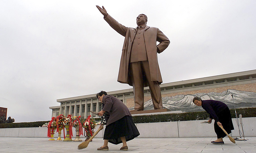 "STATUE OF LIMITATIONS: Pyongyang street sweepers tidy the area around a monument of the ""Great Leader,"" Kim Il-sung. The late despot is credited with green-lighting North Korea's first golf course."