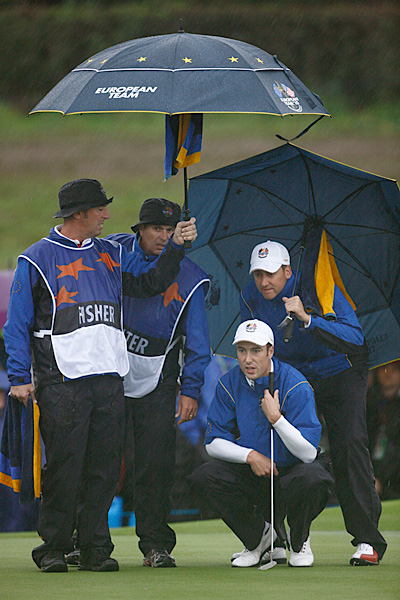 Poulter and Fisher were 1 up on Woods and Stricker when rain halted play.