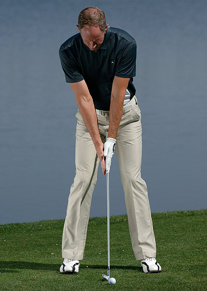 Tilt right for pure contact                           How to set yourself up to nail the ball                           By Scott Sacket                           Top 100 Teacher                                                      The problem                                                      •  You often hit the ball fat                            •  You think your head should be directly over the ball at address                                                      The solution                                                       Take a look at your grip. The first thing you should notice is that your right hand is lower than your left. So unless your right arm is five inches longer than your left (not likely), your right arm, shoulder and right side of your head should be lower than their counterparts. This means that you should be tilted at least a couple of inches to the right at both address and at impact. If you try to force your upper body to stay level at address, your club will end up bottoming out a couple of inches behind the ball, and that's when you hit it fat.                                                      To make sure that you're tilted correctly to the right at address, try these steps.                                                      1 Take your normal address position with a club, but put your hands together in a praying position in front of the handle.