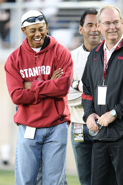 Tiger laughs on the sidelines at a 2011 Stanford football game. We are laughing at the lack of tailoring. Loving your team is no excuse for wearing a XXXL sweater, Tiger.