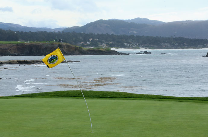 The flagstick on the 18th hole bends in the wind during a weather delay during the third round of the AT&T Pebble Beach National Pro-Am at the Pebble Beach Golf Links on Sunday.