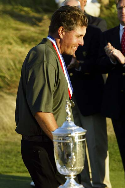 Phil Mickelson walks by the champion's trophy at the end of the U.S. Open golf championship at Shinnecock Hills Golf Club in Southampton, New York, June 20, 2004. Mickelson finished two shots behind winner, South African Retief Goosen, who shot a four-under-par 276.