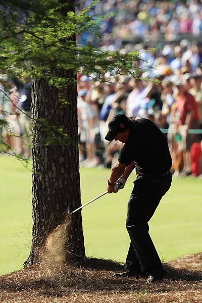 Phil Mickelson plays his famous shot from the pine needles on the 13th hole during the final round of the 2010 Masters Tournament at Augusta National Golf Club on April 11, 2010 in Augusta, Georgia. Mickelson won the tournament after a birdie on 13.