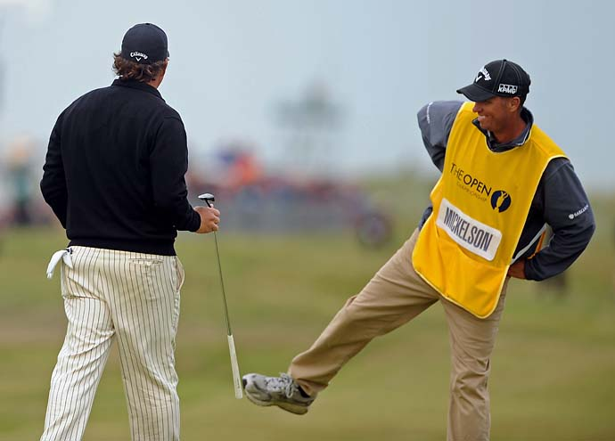 Phil Mickelson's caddie Bones Mackay kicks Mickelson's putter after a lucky shot on the 18th green in the first round of the 2011 Open Championship at Royal St. Georges Golf Course.