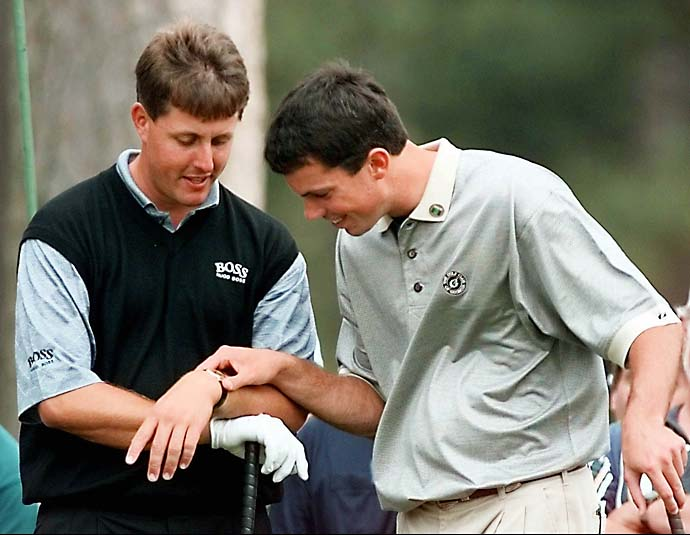 Matt Kuchar checks Phil Mickelson's watch while waiting their turn to hit on the 15th tee of the Augusta National Golf Club during the final day of practice for the 1998 Masters in Augusta, Ga., Wednesday, April 8, 1998.