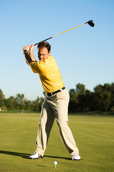 At the top, focus on driving your right hip and knee so that they arrive at impact at the same time.