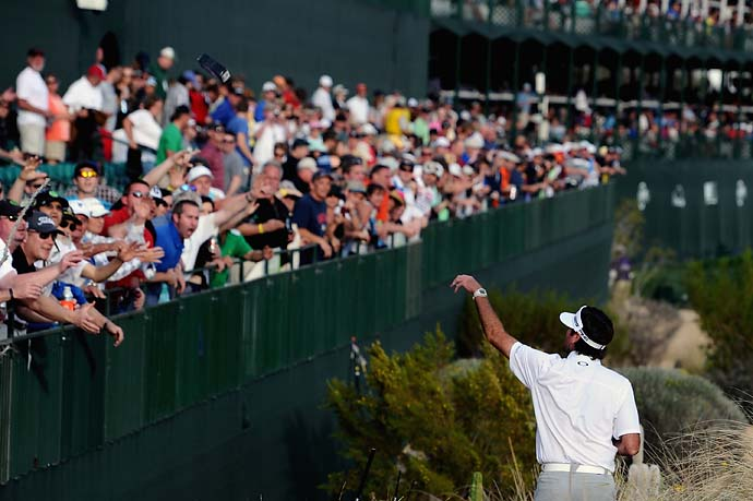 Bubba Watson tosses gifts into the crowd on the 16th hole during the first round of the Waste Management Phoenix Open at TPC Scottsdale.