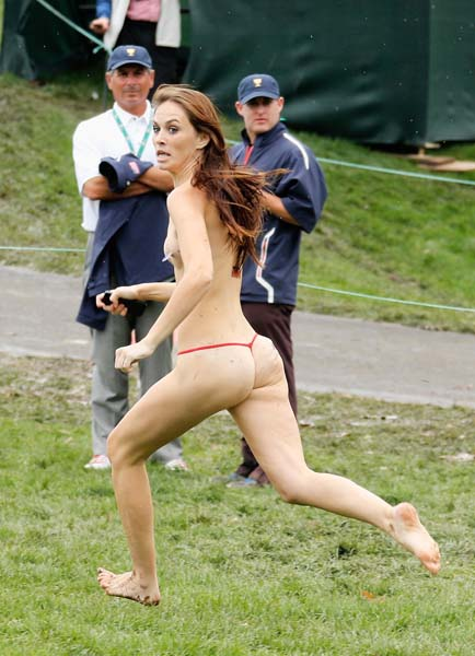 Streaker Kimberly Webster runs past an amused Fred Couples on Day 4 of the Presidents Cup at Muirfield Village Golf Club in Dublin, Ohio, on Oct. 6, 2013.