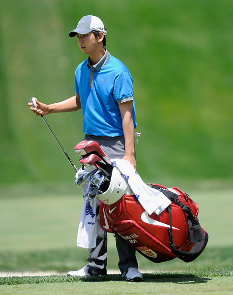 Seung-Yul Noh moves his own bag on the 13th green during the third round of the Quicken Loans National at Congressional Country Club.