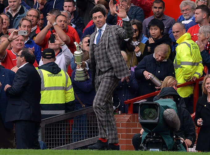 With a suit that would make more news than his appearance at the game, McIlroy appeared at half time with his British open golf trophy during the English Premier League football match between Manchester United and Swansea City at Old Trafford in Manchester.