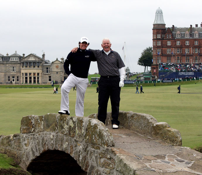 "Rory McIlroy: ""Perhaps accurately called golf's rightful home, St. Andrews tops my list for links courses. For me, it's the layout, undulations, quirky holes and just so much history. The Road Hole, No. 17, is probably my favourite, but a good round can quickly become undone here. The town of St. Andrews really sets the tone, too. There's just such a great atmosphere about the place -- golfers, spectators and a great student population as well.""                                                      Pictured: Rory McIlroy and his father and playing partner Gerry McIlroy pose for a photograph on the Swilcan Bridge on the 18th hole during the second round of The Alfred Dunhill Links Championship at The Old Course on October 2, 2009."