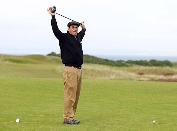Huey Lewis stretched out before playing a practice round at Kingsbarns.