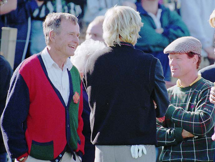 Former President George H. W. Bush talks with Greg Norman and Tom Watson on the 17th hole of the Old Course at St. Andrews during the second round of the British Open, Friday July 21, 1995.