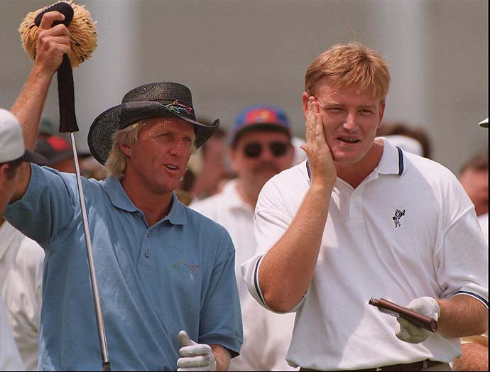 Greg Norman grabs his driver as Ernie Els  puts on sunscreen as they prepare to tee off on the ninth tee at the U.S. Open in Bloomfield Hills, Mich., Tuesday, June 11, 1996, during a practice round.