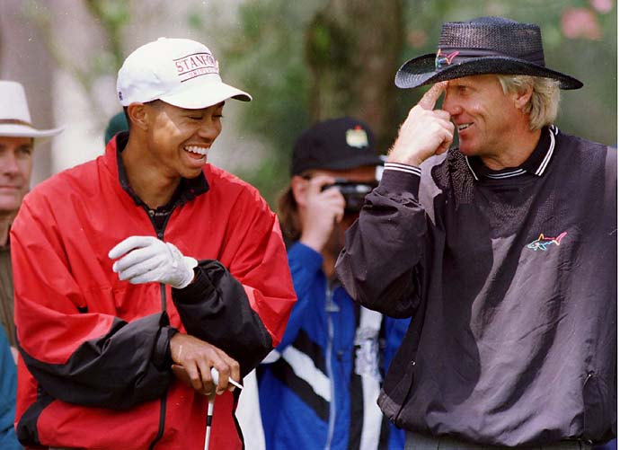 Tiger Woods and Greg Norman share a laugh on the ninth green during the second day of practice for the 1996 Masters.
