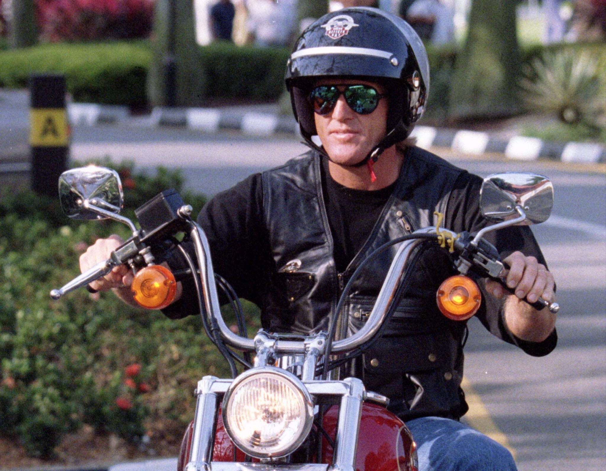 The number-one ranked golfer in the world, Greg Norman sports leather, sunglasses and a Harley helmet and as he arrives at the Johnnie Walker Classic on a Harley Davidson motorcycle in Singapore on Jan. 27, 1996.