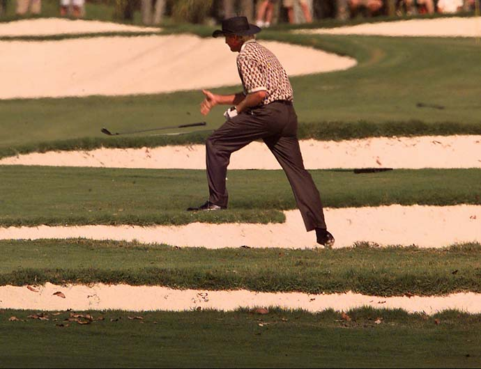 "Greg Norman throws his wedge to the ground after hitting out of a sand bunker on the first hole of the re-designed ""Blue Monster"" course  during first round play of the Doral Ryder Open in Miami on March 6, 1997."