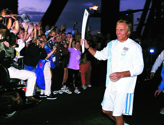 Greg Norman carries the Olympic torch across the Sydney Harbour Bridge at dawn Sept. 15, 2000, as the flame neared the end of its 100-day odyssey across the country.