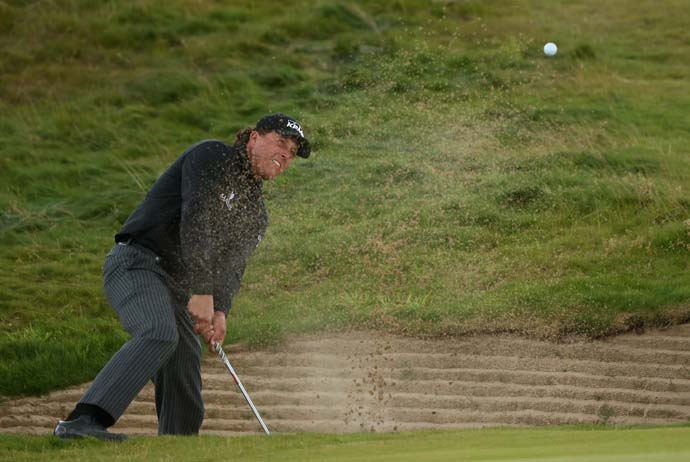 Phil Mickelson hits a shot from a pot bunker on the 16th hole of Castle Stuart Golf Links on Sunday. Mickelson played the Scottish Open as a tune-up for this week's British Open at Muirfield.