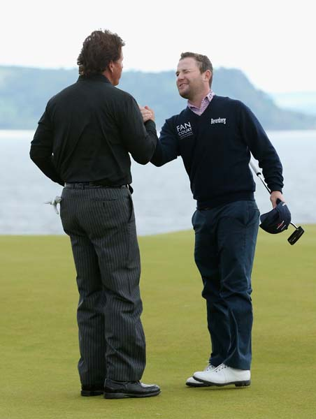 Phil Mickelson and Branden Grace shake ends after Mickelson won their first playoff hole Sunday.
