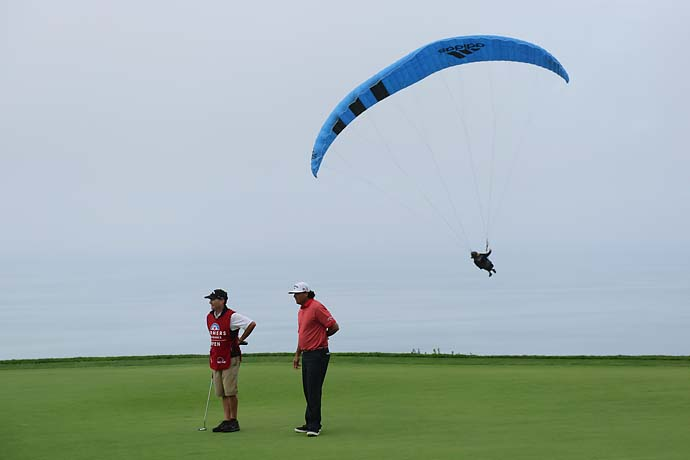 A paraglider flies over Pat Perez on the 4th green during the final round of the Farmers Insurance Open on Torrey Pines South on January 26, 2014 in La Jolla, Calif.