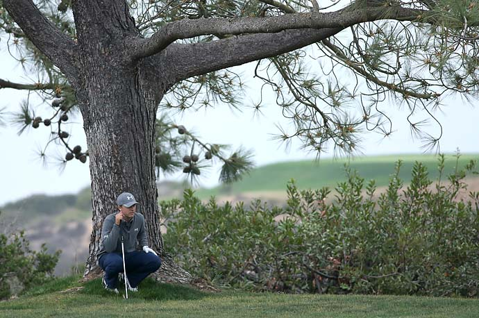 Jordan Spieth kneels by a tree as he plans his shot from the rough on the 17th hole during the final round of the Farmers Insurance Open.