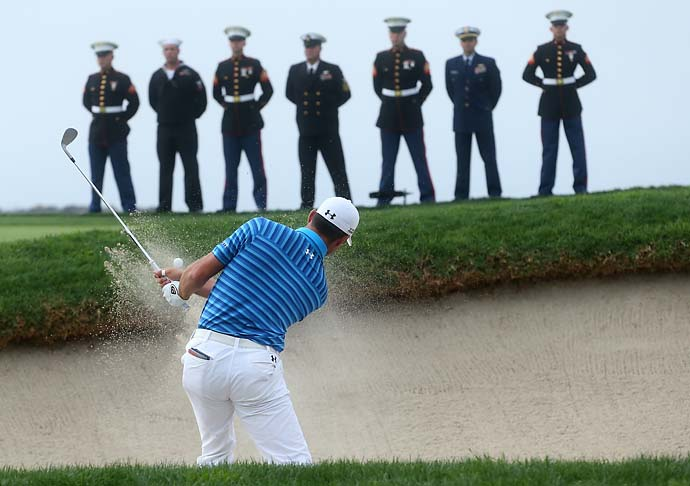 Gary Woodland hits out of a bunker on the 14th hole as military personal stand on the back of the green during the final round of the Farmers Insurance Open on Torrey Pines South on Sunday.