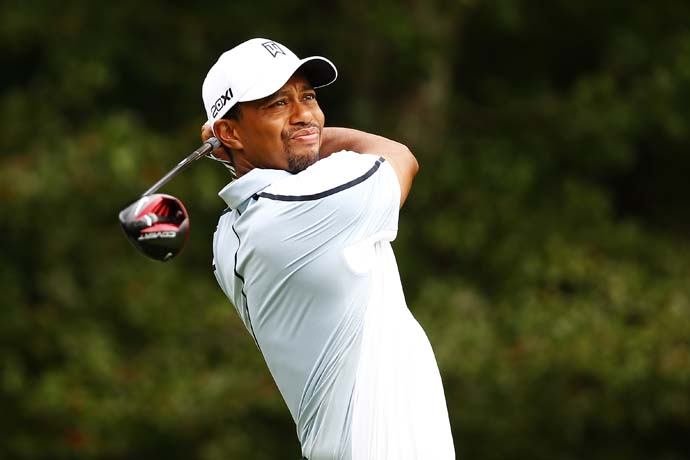 Tiger Woods hits his tee shot on the 4th hole Saturday. Woods did not appear to have back problems during his round.