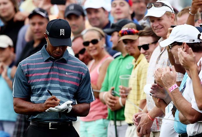 Tiger Woods signs an autograph for a fan on the first hole of the Barclays at Liberty National in Jersey City on Friday. Woods was unable to complete his second round due to darkness.