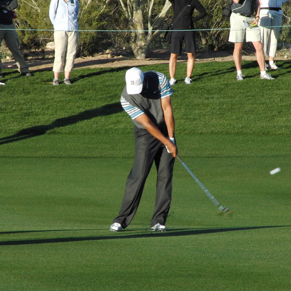 You can see Tiger's slight swing adjustment here. His left knee remains more flexed later into the swing than in the past. His left leg has always snapped straight through impact more with his driver than his irons, but this slight knee bend is new. Whether this is a conscious move or defensive mechanism, it takes pressure off the knee.