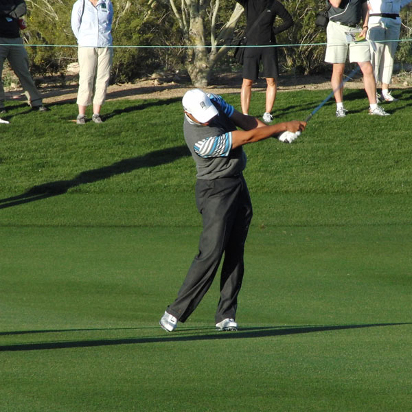 Tiger's upper body moves through toward the target with ease. His left knee is still slightly flexed, a clear difference from past years. The slight flaring of his left foot at address allows his left ankle and knee to rotate with greater ease. Tiger matches his late set of the wrists during the backswing with tremendous extension on the follow-through.