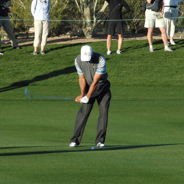 "This is what's called a ""stacked"" left side. Tiger's left shoulder, left hip, left knee and left foot are in a straight line perpendicular to the ground. This is critical because it allows his weight to be spread evenly across his left foot. The left shoulder is critical to getting stacked; it stays lower than the right shoulder late into the downswing, keeping the weight moving into his left side."