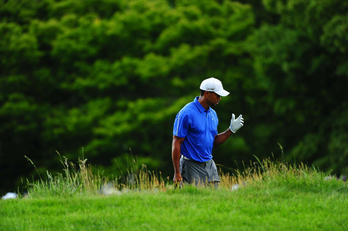 Woods grimaced in pain and shook his left arm after several shots out of the rough.