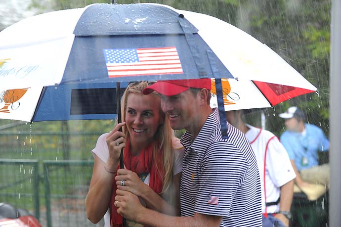 Dowd Simpson and Webb Simpson keep dry during the Day Two fourball matches.
